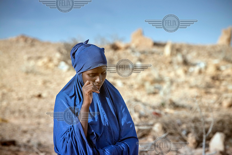 Ayan Said, 23, stands near the grave of her four year old son who died as a result of the famine. <br /> <br /> Until a year ago Ayan and her family had a herd of 300 sheep worth up to USD24,000. She said: 'We were busy then, we used to be busy all the time, trading animals, feeding them, looking after them. It was our life, we had plenty of food then. <br /> Due to the drought, six months ago the sheep started dying of starvation and illness. Within two months Ayan and her family were left with only ten sheep and decided to move to Garadag to look for help, they were almost destitute. <br /> Ayan said: 'We lost everything. We had nothing left, not even food for the ten sheep we had left. We tried to move to Garadag to access help.' Sadly, just a couple of months after they moved to Garadag, Ayan&rsquo;s youngest son, Tawkal, who was two years old,  fell ill with diahorrea and flu and died  within 15 days.<br /> Ayan said: 'We couldn't do anything for him. I couldn't take him to hospital, I couldn't give him the medicine or the food he needed. There was nothing we could do.<br /> 'I am not well. Now I worry all the time. I am alone here with one child at the moment, and I am terrified by hunger and thirst. I have nightmares about that. We have no water, no food or shelter. My child did not die suddenly, but I couldn't do anything about it.'<br /> The Horn of Africa is experiencing a devastating drought with over 11m people threatened by famine.