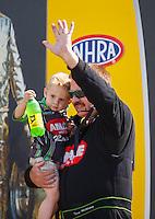 May 22, 2016; Topeka, KS, USA; NHRA top fuel driver Terry McMillen holds son Cameron McMillen during the Kansas Nationals at Heartland Park Topeka. Mandatory Credit: Mark J. Rebilas-USA TODAY Sports