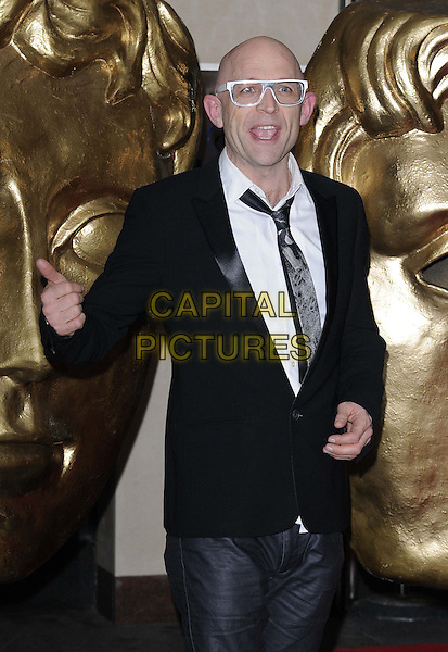 Jason Bradbury.attended the British Academy ( BAFTA ) Video Game Awards, London Hilton Park Lane Hotel, London, England..March 5th, 2013.half length black suit white shirt tie grey gray glasses jeans denim hand arm mouth open funny .CAP/CAN.©Can Nguyen/Capital Pictures.