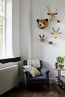 A living room with a grey armchair, a patterned cushion atop. Animal heads hang on the wall above.