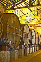 Chateau St Martin de la Garrigue. Languedoc. Barrel cellar. Wooden fermentation and storage tanks. Illuminated cellar. Wooden cross-beam roof. France. Europe.