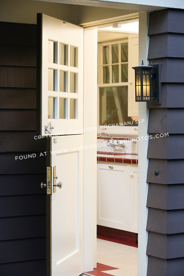 A dutch door offers entry into the red and white kitchen from the back porch of this home.