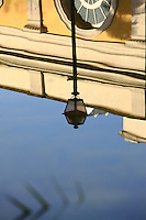 The reflected slightly distorted image of the top part of the old main building (with the half of a circular window) and of a street lamp in the nearly flat (apart from a pleating) water surface of the near basin in villa Torlonia, Rome. Digitally Improved Photo.