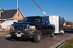 Black Ford F-250 Super Duty towing enclosed work trailer at construction site.