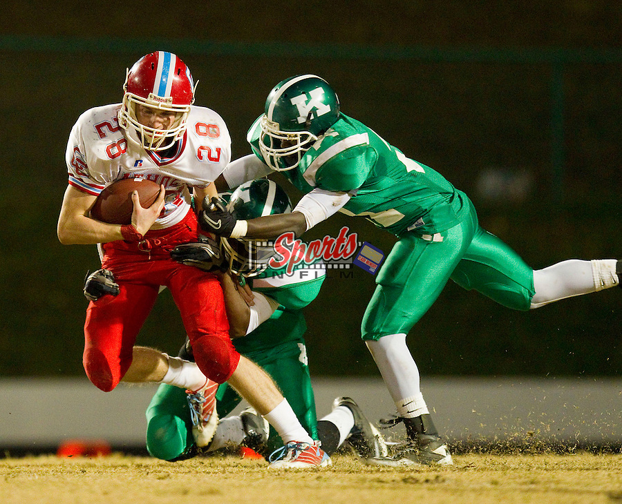 David Herlocker (28) of the Charlotte Catholic Cougars is tackled by two A.L. Brown defenders at A.L. Brown High School on November 26, 2010 in Kannapolis, North Carolina.  The Cougars defeated the Wonders 45-7.  (Brian Westerholt/Sports On Film)