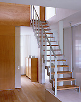 This contemporary hallway features an open staircase and sliding doors