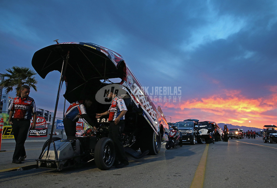 Apr. 5, 2013; Las Vegas, NV, USA: The sun sets behind NHRA funny car driver Courtney Force in the staging lanes during qualifying for the Summitracing.com Nationals at the Strip at Las Vegas Motor Speedway. Mandatory Credit: Mark J. Rebilas-