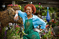 An african-american woman stands proudly with a smile on her face inside her garden.