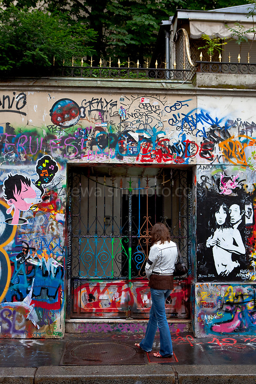 A woman pauses outside the house of Serge Gainsbourg, 5 Bis Rue de Verneuil, 75006 Paris, France.  La maison de Serge Gainsbourg.