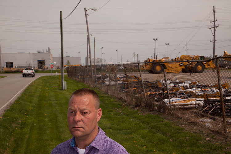 Denny Ryder was laid off from Caterpillar in late 2013, and left Decatur, his hometown, to work for a Caterpillar contractor in North Carolina. Ryder is shown during a return visit in front of the Caterpillar plant and Keen Transport, right. Longtime industrial city Decatur, Ill., had the country&rsquo;s greatest unemployment rate reduction. But people leaving the workforce &ndash; moving away, retiring, no longer looking for jobs -- may be the cause, rather than economic expansion. <br /> CREDIT: Kristen Schmid for the Wall Street Journal<br /> RUSTBELT