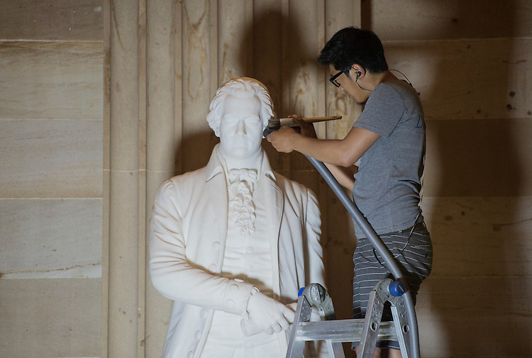 UNITED STATES - JUNE 16: Gompo Yarmolinsky, of Daedalus Conservators, vacuums dust from the Alexander Hamilton statue in the Capitol Rotunda on Tuesday evening, June 16, 2015. (Photo By Bill Clark/CQ Roll Call)