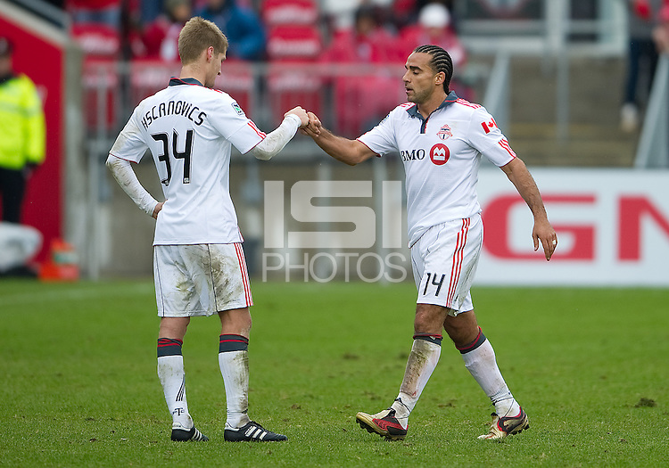 25 April 2010: Toronto FC midfielder Dwayne De Rosario #14 goes off during a substitution as Toronto FC defender Raivis Hscanovics #34 shows his appreciation during a game between the Seattle Sounders and Toronto FC at BMO Field in Toronto..Toronto FC won 2-0....