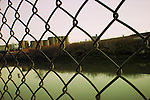 View through a fence with industrial area and polluted water. Brooklyn, New York.