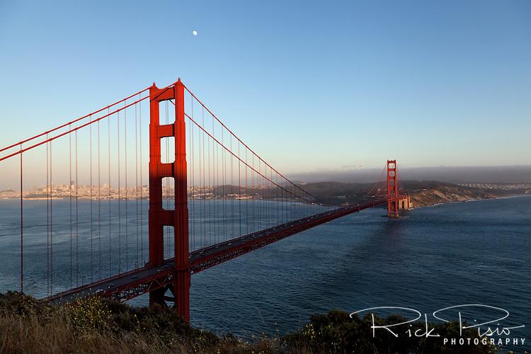 Full moon over the Golden Gate Bridge at dusk.
