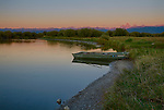 Idaho, Eastern, Teton Valley,  A rowboat on the shore of the Teton River beneath the alpine glow of a late summer sunset in Eastern Idaho.