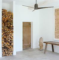 In the studio a tall alcove is piled high with logs for winter whilst there is also a ceiling fan for hot summer weather