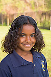 Portrait of smiling seven year old mixed ethnicity black female in school uniform outdoors