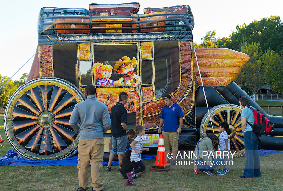 Old Bethpage, New York, U.S. 29th September 2013. Children are bouncing inside the Deadwood & Cheyenne stagecoach ride at The Long Island Fair. A yearly event since 1842, the county fair is now held at a reconstructed fairground at Old Bethpage Village Restoration.