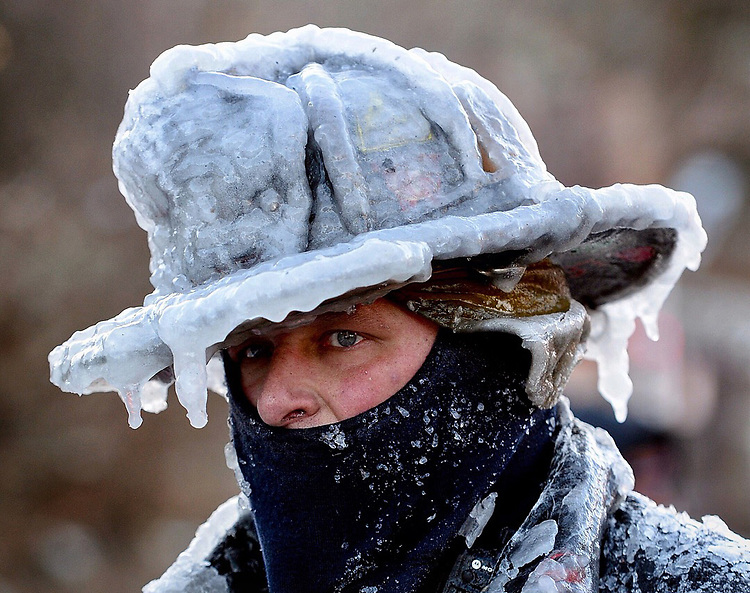 (Nahant, MA, 01/01/18) Lynn firefighter Bobby Lehman with his helmet and bunker gear caked in ice tries to thaw out after battling a stubborn, wind-driven fire at 238 Wilson Road in Nahant on Monday, January 01, 2018. Photo by Christopher Evans
