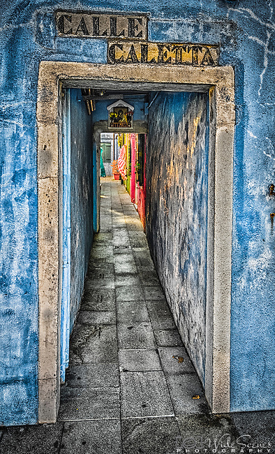 A narrow alleyway on the island of Burano in Venice, Italy. Burano is an island in the Venetian Lagoon and is located 7 kilometres (4 miles) from Venice, a short 40 minute trip by ferry.