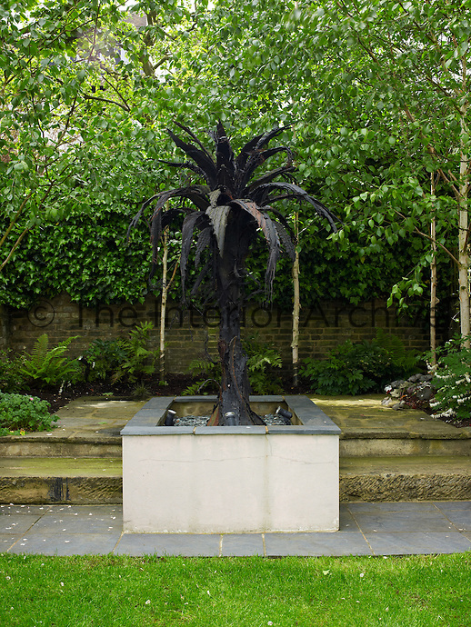 A bronze sculpture in the shape of a palm tree is displayed on a plinth in the garden