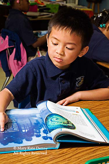 One Vietnamese American male seven year old in second grade classroom reads a book at his desk in New Orleans.