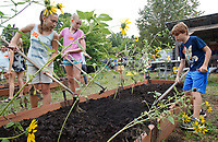 NWA Democrat-Gazette/DAVID GOTTSCHALK Iris Scharnhorst (from left), 12, Luna Richter, 12, and Grayson Waddle, 8, break up the soil in one of the beds Wednesday, August 8, 2018, with students participating in the Washington Elementary School Garden Club Back to School Summer Camp at the school in Fayetteville. The campers are prepping and planting a fall garden at the school and participating in recreational and educational activities in the surrounding neighborhood.