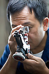 Kazuhito Komatsu, president of Komatsu Cutting Factory, looks through a loupe at a precious stone he is cutting and processing at his company in Kofu City, Yamanashi Prefecture, Japan on 16 Oct. 2012.   Photographer: Robert Gilhooly