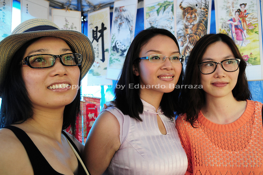 Mesa, Arizona. November 4, 2012 - Ai Ling (left), Xin Huag (center), and Yan Huang (right), enjoy the 18th Annual Asian Festival 2012 by looking at merchandise at Bali Art booth. The three young women are originally from Guanzhong, China and have living been in the U.S. For the last two years. In Arizona, Asian-Americans celebrated a colorful festival where their rich culture was admired and their growing presence affirmed. Asian-Americans are now the United States fastest-growing racial group, the best-educated and highest-earning workers. Photo by Eduardo Barraza © 2012