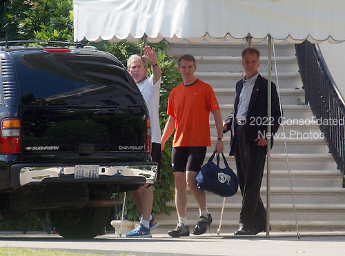 United States President George W. Bush, in white shirt, waves as he prepares to depart the White House to go Mountain Biking with United States Trade Representative Rob Portman, in orange shirt, on June 23, 2005. <br /> Credit: Ron Sachs - Pool