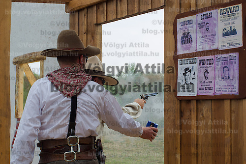 Competitor (back) fires his weapon during the Cowboy Action Shooting European Championship in Dabas, Hungary on August 11, 2012. ATTILA VOLGYI