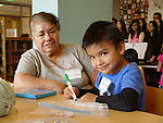 A student from Laurenzo Early Childhood Center creates a simple bookmark with a member of the East Early College High School honor society, as his grandmother looks on, as part of Family Literacy Day on Dec. 12, 2014.