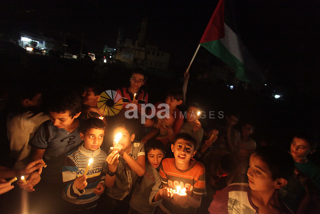 Palestinian children hold candles during a protest against power cuts in Gaza City November 3, 2013. Gaza's lone power plant shut its generators on Friday due to a fuel shortage, a move that will likely increase already long blackout hours in the impoverished coastal territory run by the Islamist Hamas group. Photo by Ashraf Amra