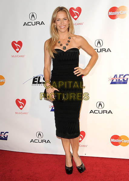 SHERYL CROW .at The 2010 Musicares Person of The Year Tribute to Neil Young held at The L.A. Convention Center in Los Angeles, California, USA, January 29th 2010                                                                   .full length  black dress strapless hand on hip pattern print patent platform shoes clutch bag .CAP/RKE/DVS.©DVS/RockinExposures/Capital Pictures
