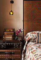 The master bedroom embraces strong colours as an accent. Orange thread weaves through the embroidered Donghia fabric on the custom-made head board and is complimented with a bed cover made from fabric. An Andrew Martin steamer trunk acts as a bedside table.