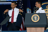 Annapolis, Maryland - May 22, 2009 -- United States President Barack Obama, left, tries on a jacket given to him by the class of 2009 at the 2009 U.S. Naval Academy Graduation. .Credit: Kristoffer Tripplaar-Pool via CNP
