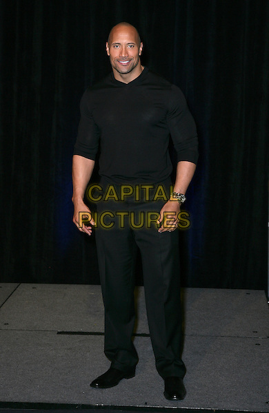 "DWAYNE ""The Rock"" JOHNSON.CBS Films ShoWest Luncheon at the Paris Resort Hotel and Casino,  Las Vegas, Nevada, USA,.18th March 2010..full length black jumper sweater trousers .CAP/ADM/MJT.© MJT/AdMedia/Capital Pictures."