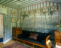 A grisaille papier peint is displayed in panels against the blue and white striped wallpaper of this tented dressing room