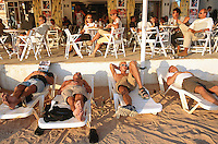 Spain. Ibiza in the Balearic islands. San Antonio. Mediterranean sea. Some tourists enjoy a drink on the terrace of the Café del Mar. Young men lay on plastic chairs, they either sleep or just rest and enjoy the sun. © 1999 Didier Ruef