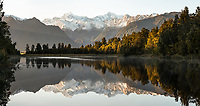 Winter dawn reflections of Mount Tasman and  Aoraki, Mount Cook of Southern Alps in Lake Matheson, Westland Tai Poutini National Park, West Coast, UNESCO World Heritage Area, South Westland, New Zealand, NZ