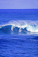 Two surfers catch an a perfect monster wave on Oahu's North shore, home of the world's best surfing. Great shot of wave beginning to curl with vertical spray coming off face of the forceful wave.