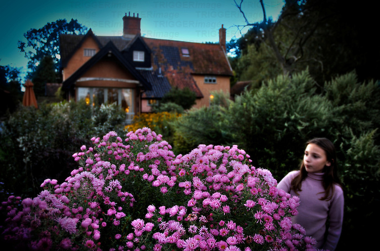 A young girl wearing a purple sweater standing in a garden next to purple flowers with a cottage in the background