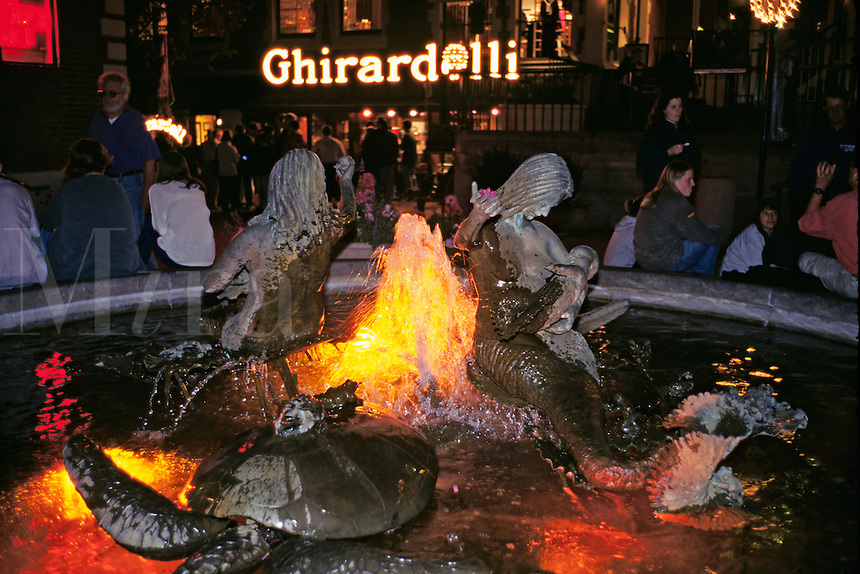 San Francisco, CA; People Sit Around Fountain At Ghirardelli Square At Nigh