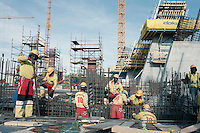 CAPE TOWN, SOUTH AFRICA - OCTOBER 24: Unidentified laborers work at the construction site of the new Green Point stadium on October 24, 2007 in the Green Point area in Cape Town, South Africa. The stadium is one of many being built and upgraded for the 2010 World Cup. The laborers wear a uniform looking as a soccer uniform. Soccer is the most popular sport in South Africa, and because of the upcoming World Cup 2010 in South Africa the interest is increasing. For the first time the World Cup will be held on the African continent. .(Photo by Per-Anders Pettersson)...