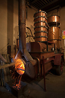 Europe/France/Midi-Pyrénées/32/Gers/Eauze: Le distillateur Jean Lenos Da Costa recharge en bois l'alambic  lors de la distillation au Domaine du Tariquet<br /> Auto N°: