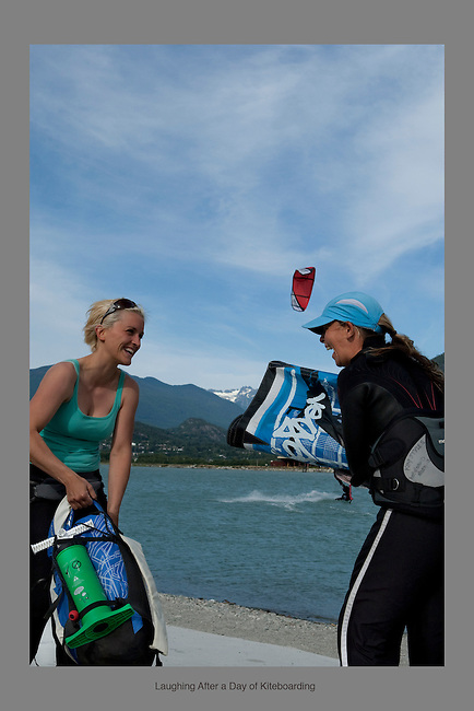 July 20th 2009. Amber Kirk (left), and Kim Styles (right), laugh as they wrap up their gear, after a day of great kiteboarding at the Spit in Squamish BC.  Photo by Gus Curtis.