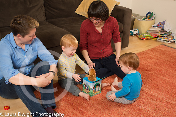 Fraternal twin boys, age 22 months, at home with parents, playing with jack in the box toy