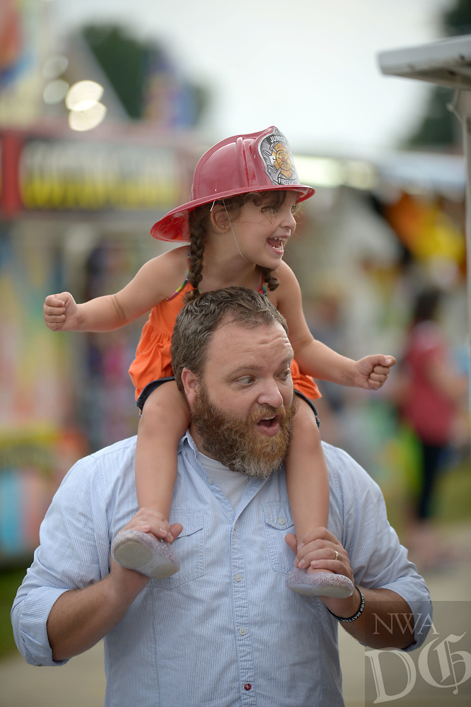NWA Democrat-Gazette/ANDY SHUPE<br /> Peyton Winn, 4, and her father, Jason Winn of Rogers, cheer Wednesday, Aug. 8, 2018, as they head out into the midway to enjoy the 120th annual Tontitown Grape Festival in Tontitown. The festival continues through Saturday. The festival features a nightly midway, an arts and crafts fair, spaghetti dinners and live entertainment.