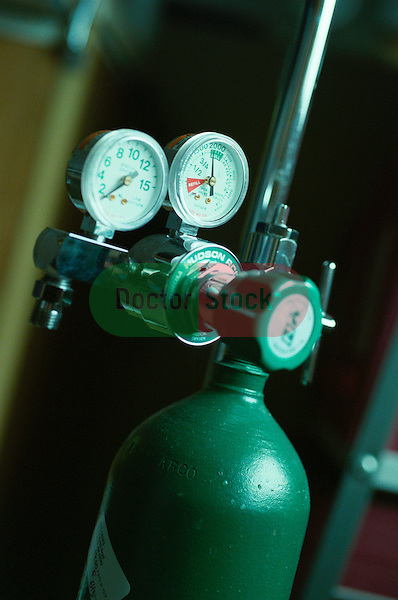 pressure gauges on top of green oxygen tank