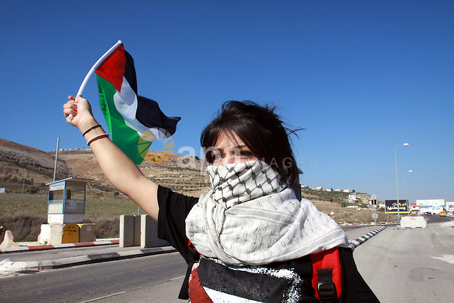 A Palestinian activist holds her national flag while she block a road leading to Huwwara checkpoint near the West Bank city of Nablus during a demonstration in support of the people of the Gaza Strip and against Israeli air strikes on November 15, 2012. Several Palestinians were killed following a series of Israel's concurrent airstrikes on Gaza city, among them was Ahmed al-Jaabari, top commander of Hamas armed wing Al-Qassam brigades, and more than 150 others wounded, government's emergency services in the Gaza Strip said. Photo by Nedal Eshtayah